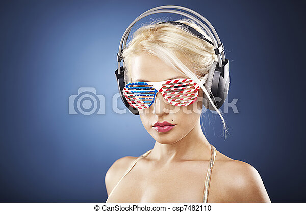 Beautiful blonde model with headphones and American inspired grid glasses dressed in gold swimwear. - csp7482110