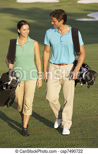Couple Walking Along Golf Course Carrying Bags - csp7490722