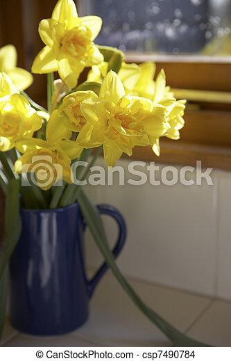 Vase Of Daffodils In Blue Jug On Window Sill - csp7490784