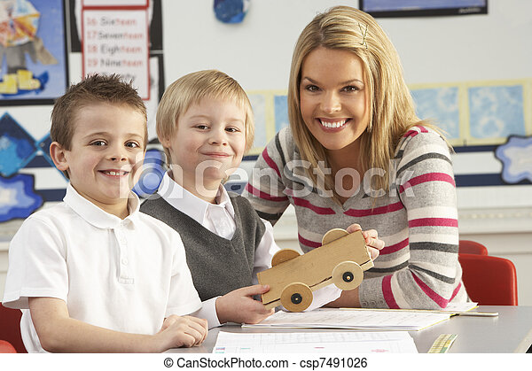 Two Male Primary School Pupils And Teacher Working At Desk In Classroom - csp7491026