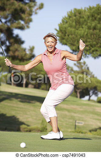 Senior Female Golfer On Golf Course Lining Up Putt On Green - csp7491043