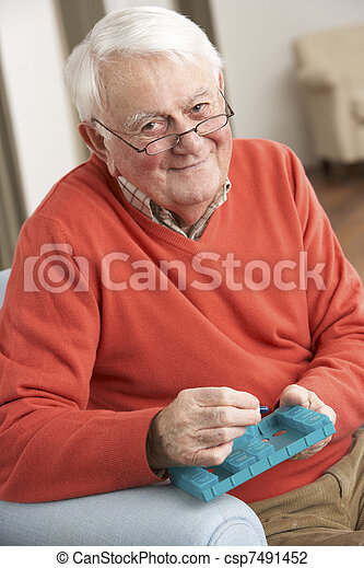 Senior Man Sorting Medication Using Organiser At Home - csp7491452