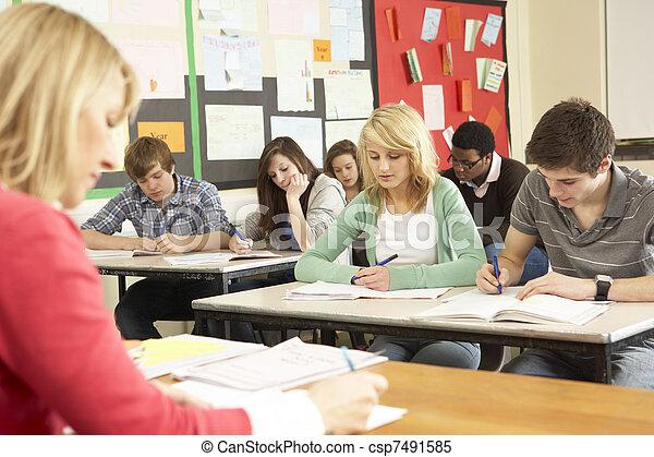 Teenage Students Studying In Classroom With Teacher - csp7491585