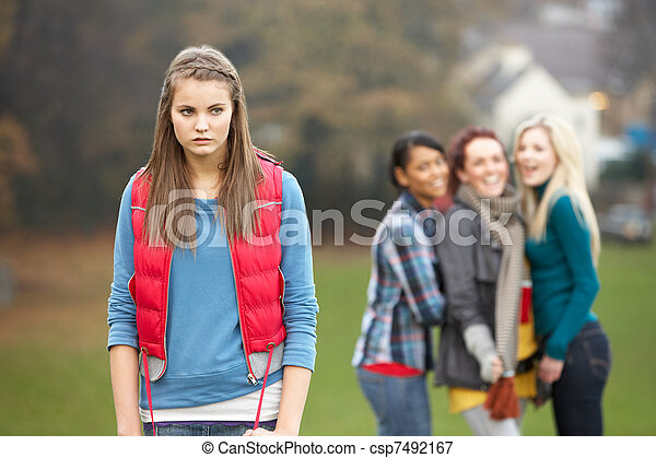 Upset Teenage Girl With Friends Gossiping In Background - csp7492167