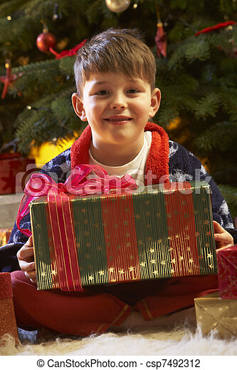 Young Boy Opening Christmas Present In Front Of Tree - csp7492312