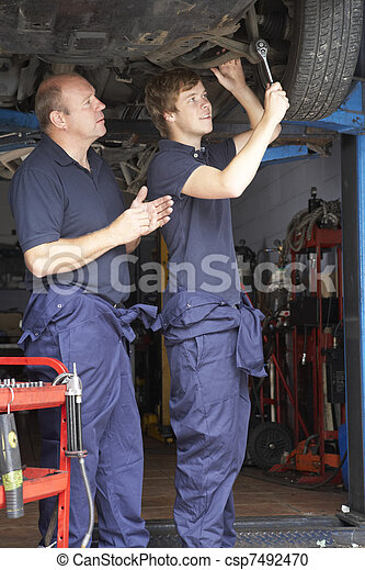 Mechanic and apprentice working on car - csp7492470