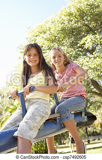 Two Girls Riding On See Saw In Playground - csp7492605