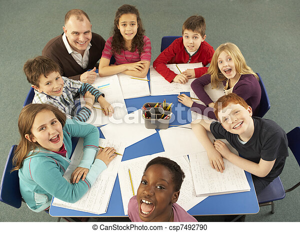 Overhead View Of Schoolchildren Working Together At Desk With Teacher
