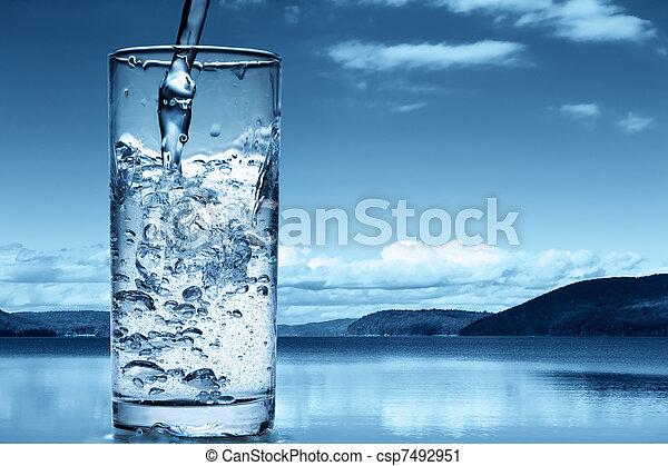 Pouring water into a glass against the nature background - csp7492951