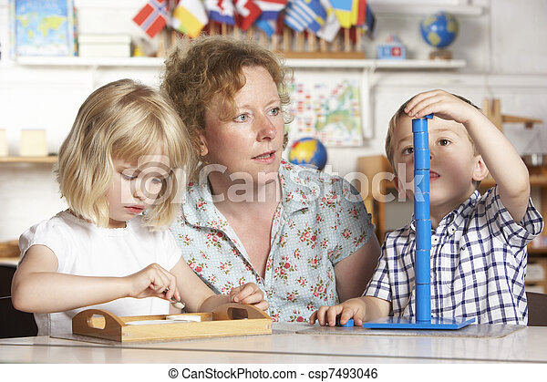 Adult Helping Two Young Children at Montessori/Pre-School - csp7493046