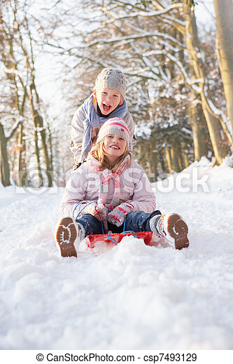 Boy And Girl Sledging Through Snowy Woodland - csp7493129