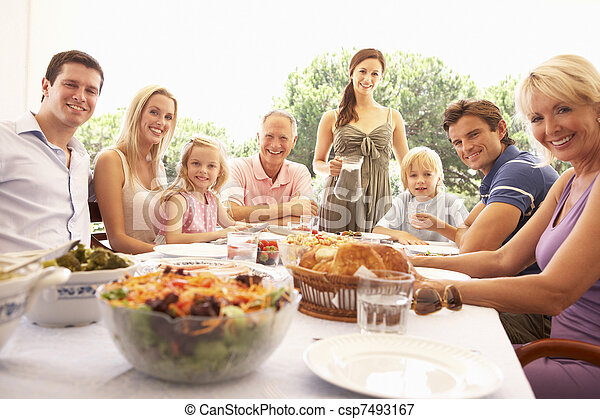 A family, with parents, children and grandparents, enjoy a picnic - csp7493167