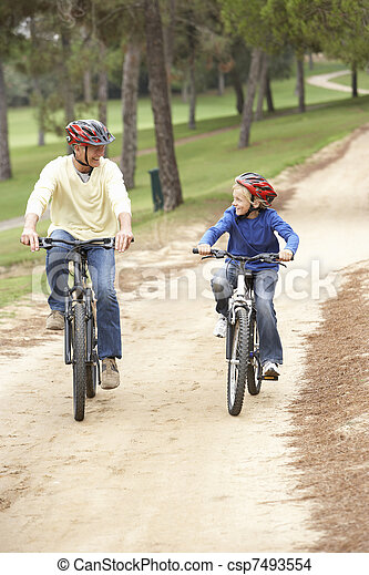 Grandfather and grandson riding bicycle in park - csp7493554