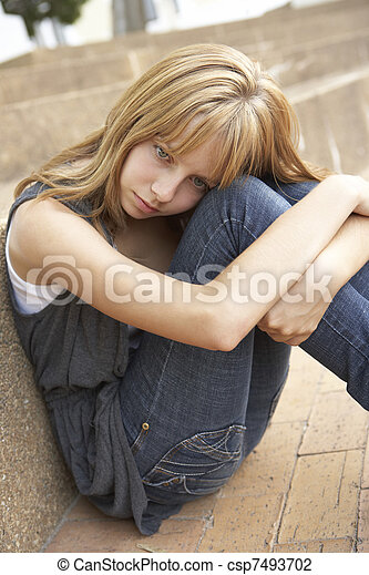 Unhappy Female Teenage Student Sitting Outside On College Steps Using Mobile Phone - csp7493702