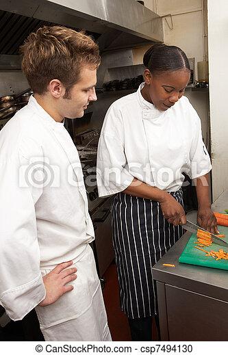 Chef Instructing Trainee In Restaurant Kitchen - csp7494130