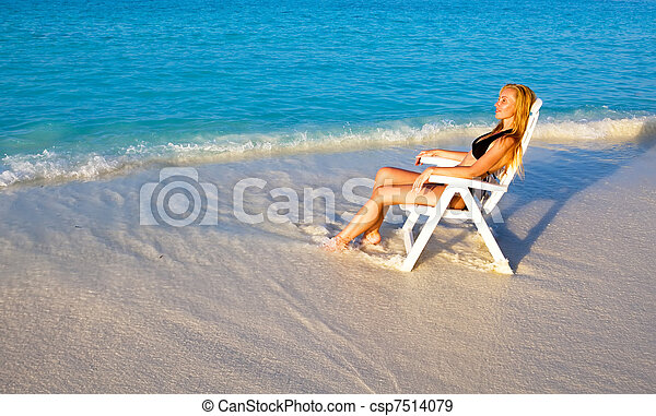 Young pretty woman tans in beach chair, it put in ocean