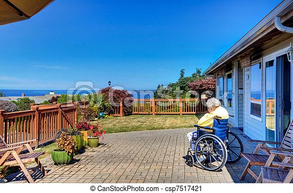 Women in handicap chair is happing in the yard - csp7517421