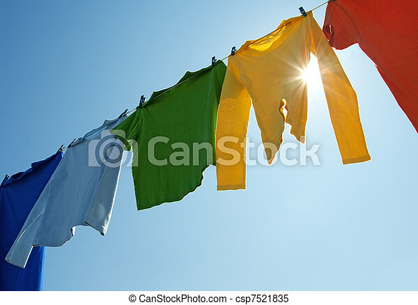 Colorful clothes on a laundry line and sun shining - csp7521835
