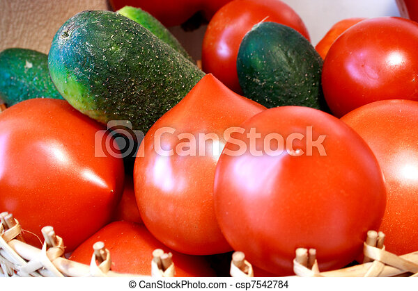 Foto of cucumber and tomatoes laying nearby - csp7542784