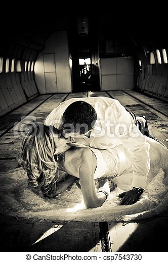 sexy young  adult wedding couple laying in the fuselage of airplance - csp7543730
