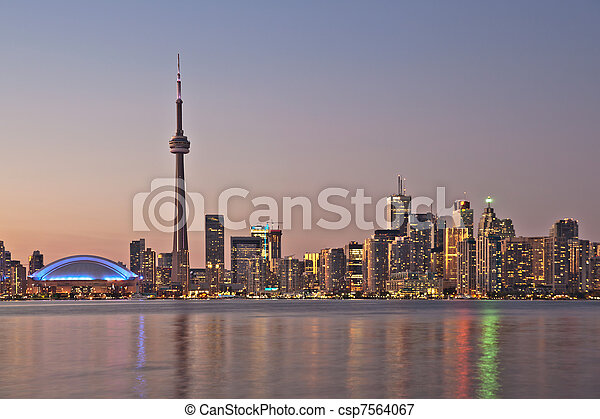 The landmark Toronto downtown view from the center island. Scenic view of the CN Tower illuminated by the iconic downtown skyline of skyscrapers and high rise condominiums reflecting in Lake Ontario  - csp7564067