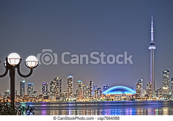 The landmark Toronto downtown view from the center island. Scenic view of the CN Tower illuminated by the iconic downtown skyline of skyscrapers and high rise condominiums reflecting in Lake Ontario  - csp7564088