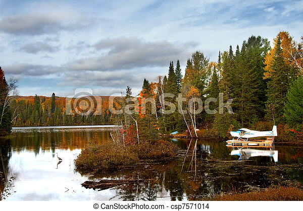 Seaplane moored to a dock on a quiet lake - csp7571014