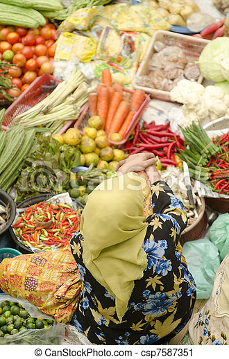 Vegetable market. Muslim woman selling fresh vegetables at Siti Khadijah Market market in Kota Bharu Malaysia.  - csp7587351