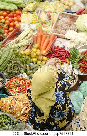 Vegetable market. Muslim woman selling fresh vegetables at Siti Khadijah Market market in Kota Bharu Malaysia. - csp7587351