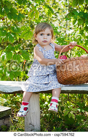 little girl sits on a bench with a basket of apples