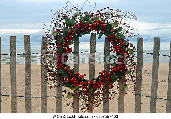 Christmas berry wreath hanging on a beach fence.