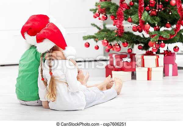 Loving siblings in front of the christmas tree - csp7606251