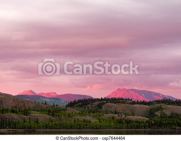 Distant Yukon mountains glowing in sunset light - csp7644464