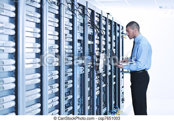 businessman with laptop in network server room - csp7651003