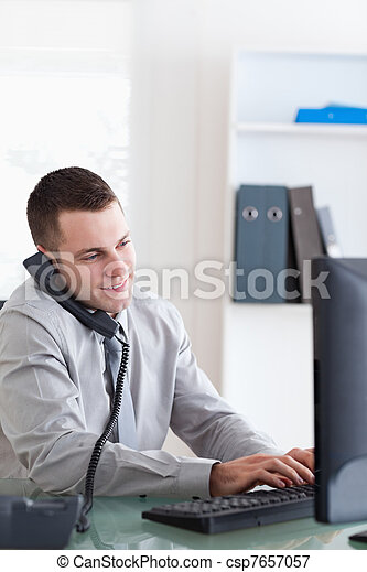 Businessman using his computer while talking on the phone - csp7657057