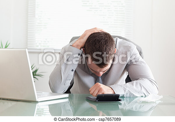 Businessman unhappy with his calculations - csp7657089