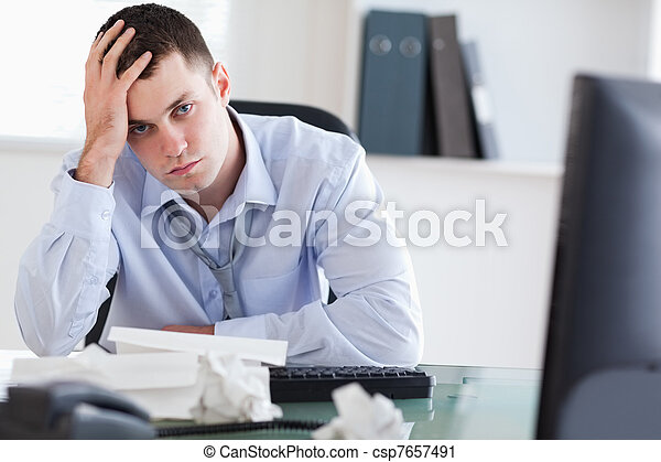 Close up of frustrated businessman doing his accounting - csp7657491