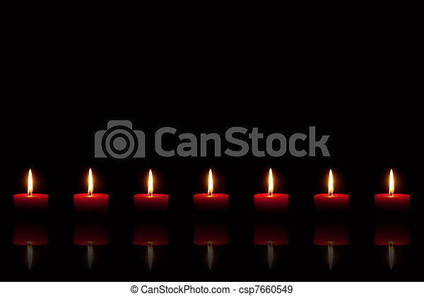 Burning red candles in front of black background - csp7660549