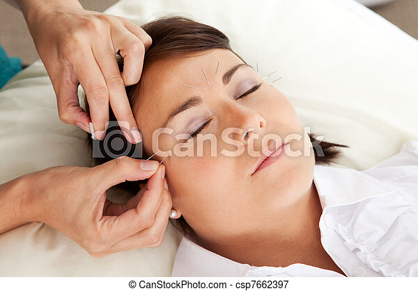 Acupuncture Therapist Placing Needle in Face - csp7662397