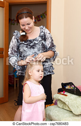 Mother plaiting pigtail her child - csp7680483