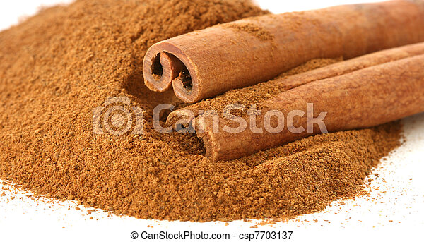 Whole cinnamon sticks on heap of ground cinnamon - csp7703137