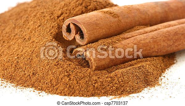 Whole cinnamon sticks on heap of ground cinnamon - csp7703137