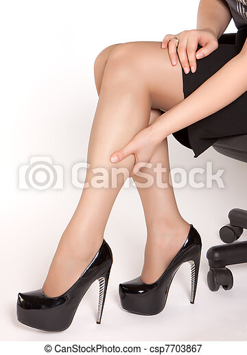 Women wearing high heels black shoes, sitting on the chair and massaging tired legs - csp7703867
