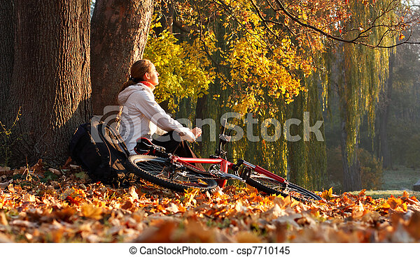 Relaxes woman cyclist with bike sits among fallen leaves autumn morning in nature illuminated by the bright rays of the rising sun and enjoy recreation - csp7710145