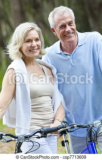 Happy Senior Man & Woman Couple Cycling Bicycles - csp7713609