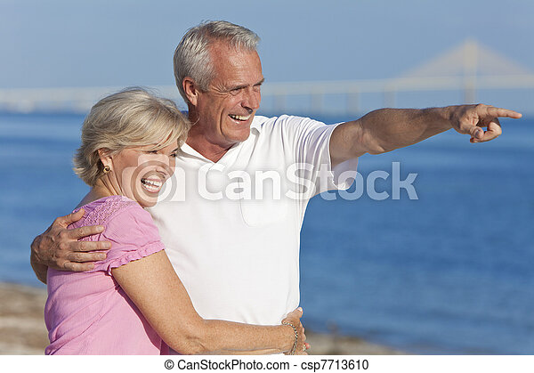 Happy Senior Couple Walking Pointing on Beach - csp7713610