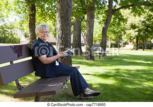 Woman reading book in a park - csp7716950