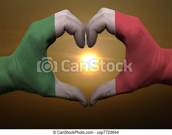 Gesture made by italy flag colored hands showing symbol of heart and love during sunrise - csp7723644