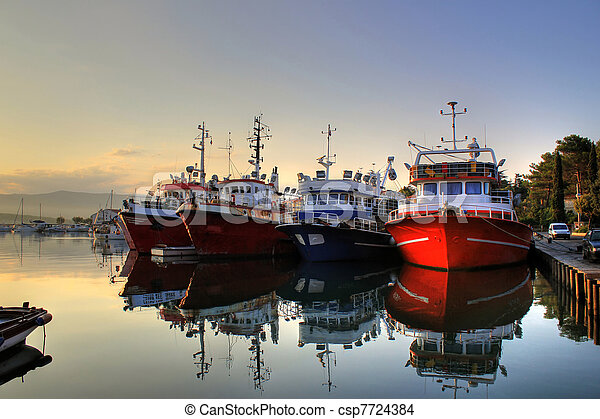 Fishing boats on early morning on calm sea - csp7724384