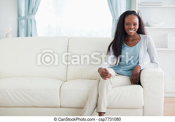 stock fotografie von frau sitzen auf sofa mit beine gekreuzt l cheln csp7731080. Black Bedroom Furniture Sets. Home Design Ideas